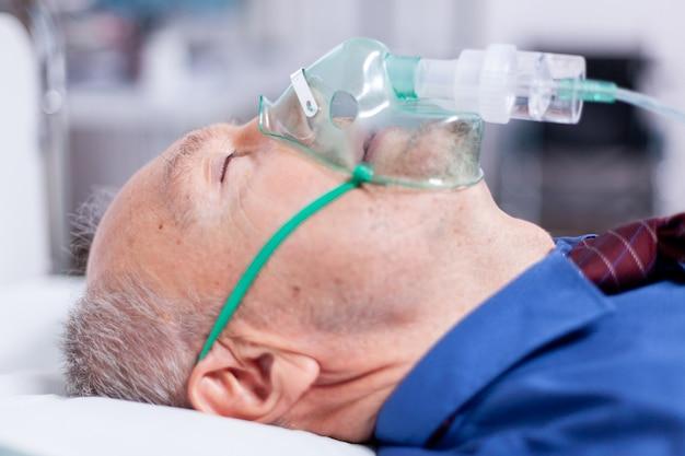 Zieke oude man met ademmasker liggend op ziekenhuisbed na besmetting met coronavirus