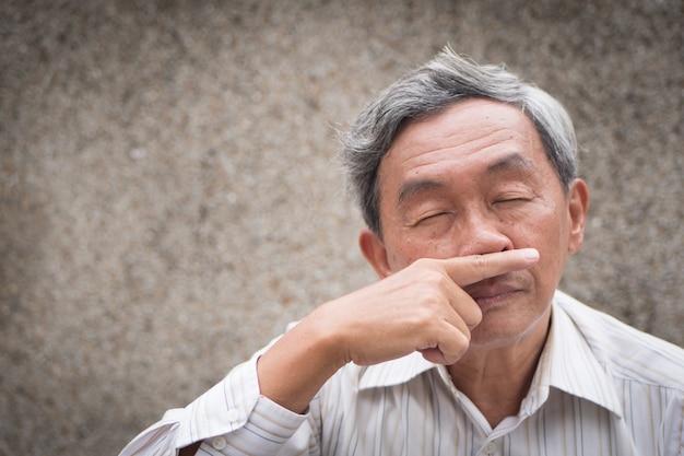 Zieke oude senior man met loopneus