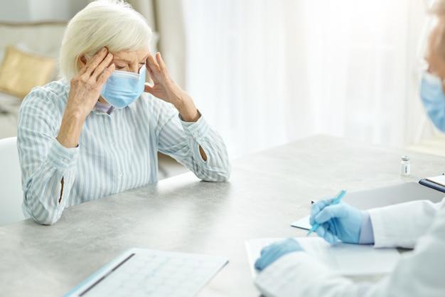 Zieke oude vrouw bespreekt gezondheidsproblemen met arts in kliniek
