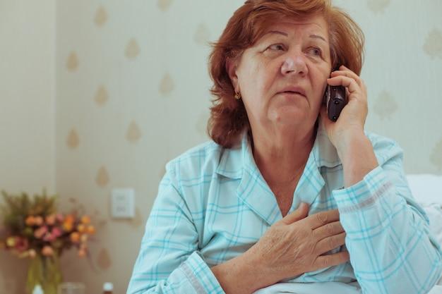 Zieke oude vrouw die haar arts belt. gezondheidszorg oude mensen concept.
