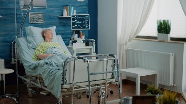 Zieke oude vrouw die in ziekenhuisbed ligt in een verpleeghuis