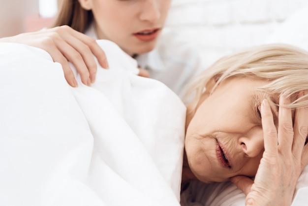 Zieke oude vrouw heeft hoofdpijn in haar slaap.