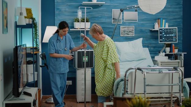 Zieke oude vrouw loopt met infuuszak en verpleegster die hulp geeft