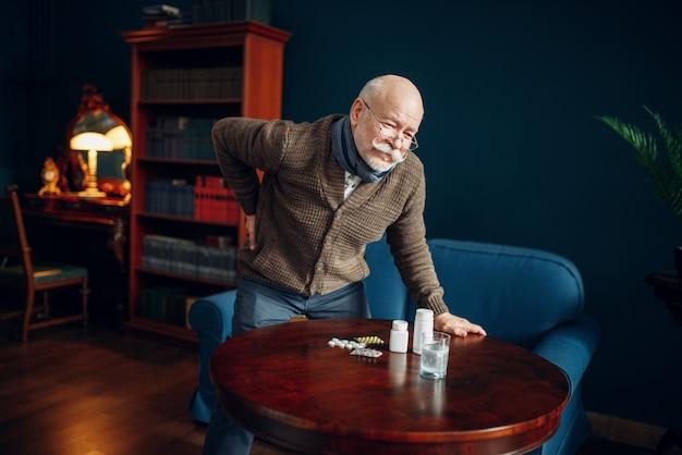 Zieke oudere man houdt zijn rug in het kantoor aan huis, aan leeftijd gerelateerde ziekten. oudere senior is ziek en wordt in zijn huis behandeld