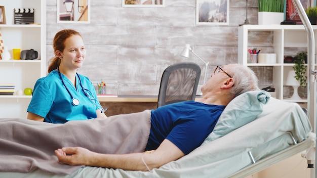 Zieke oudere man in gesprek met een blanke verpleegster terwijl hij in een ziekenhuisbed in een verpleeghuis ligt