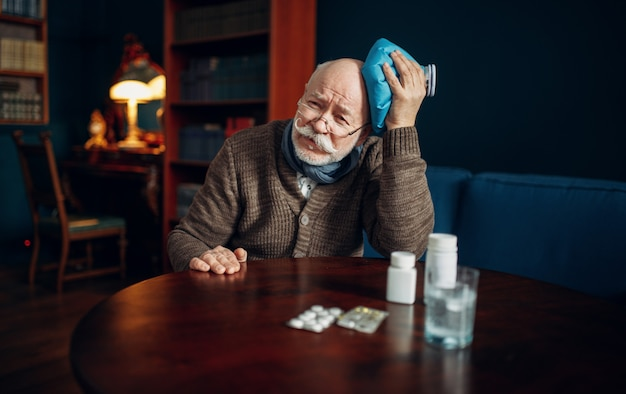 Zieke oudere man legt ijs op zijn hoofd in thuiskantoor, ouderdomsziekten, hoofdpijn. oudere senior is ziek en wordt in zijn huis behandeld