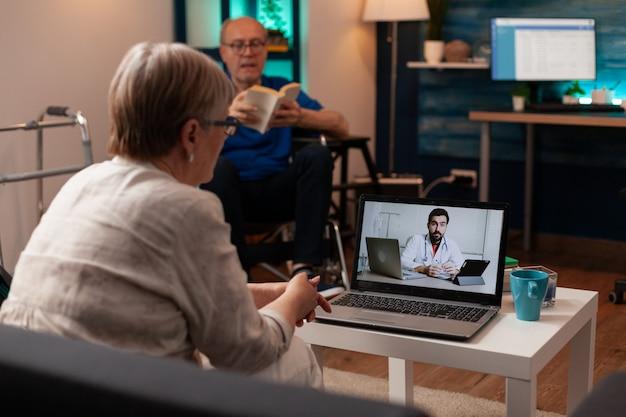 Zieke oudere patiënt die telegeneeskunde gebruikt tijdens videogesprek