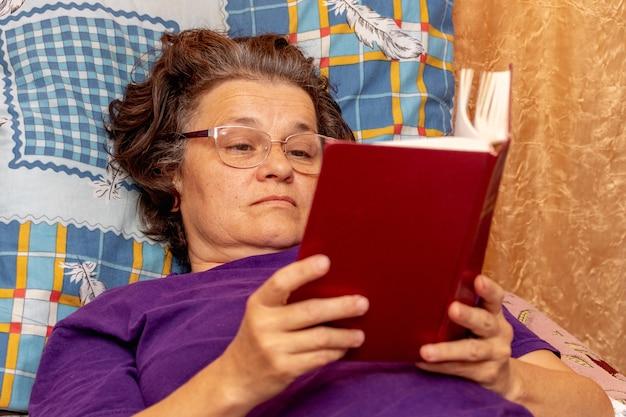 Zieke oudere vrouw die op de bank ligt en een boek leest. bijbel lezen