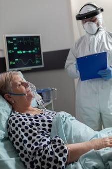 Zieke oudere vrouw inhaleert en ademt uit door zuurstofmasker dat in ziekenhuisbed ligt tijdens wereldwijde pandemie met coronavirus