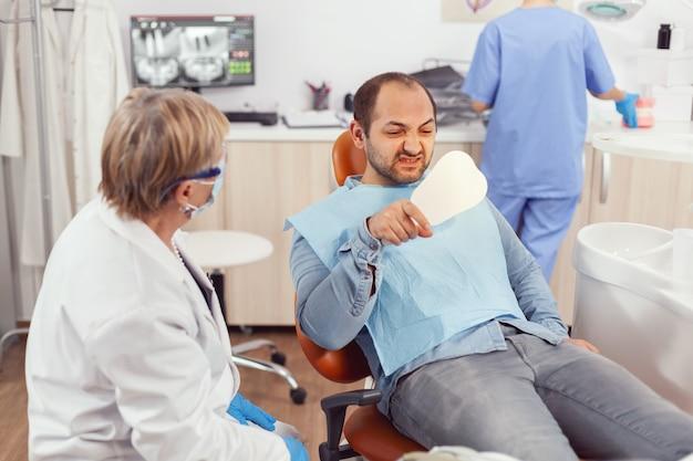 Zieke patiënt die tanden inspecteert na tandheelkundige chirurgie met behulp van spiegel terwijl hij op stomatologische stoel zit in het kantoor van de ziekenhuiskliniek
