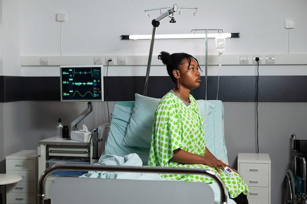 Zieke patiënt van afro-amerikaanse etniciteit die op bed ligt