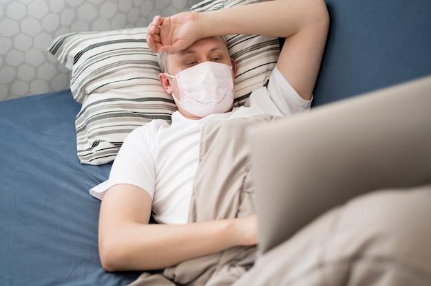 Zieke persoon die een masker binnenshuis draagt