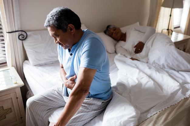 Zieke senior man die lijden aan buikpijn in de slaapkamer