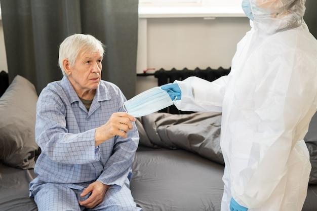Zieke senior man in blauwe pyjama die een medisch masker neemt van de gehandschoende hand van een vrouwelijke arts in beschermende overall terwijl hij thuis op de bank zit