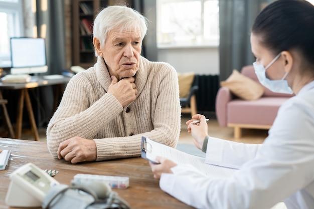 Zieke senior man kijkt naar jonge vrouwelijke arts in whitecoat en medisch masker en vertelt haar over zijn symptomen in de thuisomgeving