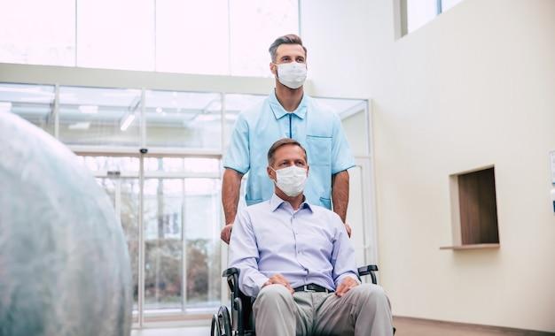 Zieke senior man met beschermend veiligheidsmasker op gezicht in een rolstoel en een zelfverzekerde arts in het medische masker tijdens het vervoer in het ziekenhuis.