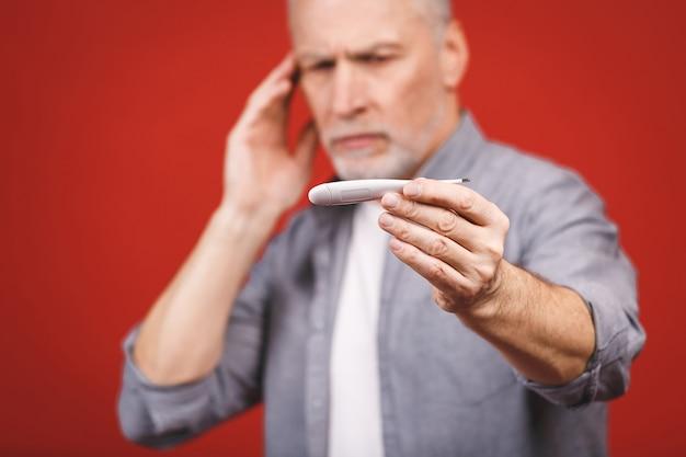 Zieke senior man met thermometer met griep, allergie, ziektekiemen, co