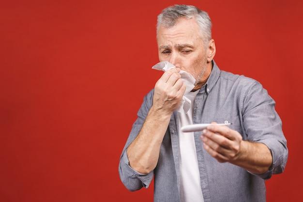 Zieke senior man met thermometer, zijn neus waait met weefsel.