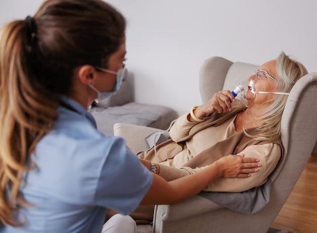 Zieke senior vrouw die thuis in de stoel zit en zuurstof uit het ademhalingsapparaat inhaleert. verpleegster zit naast haar, houdt haar hand vast en troost haar.