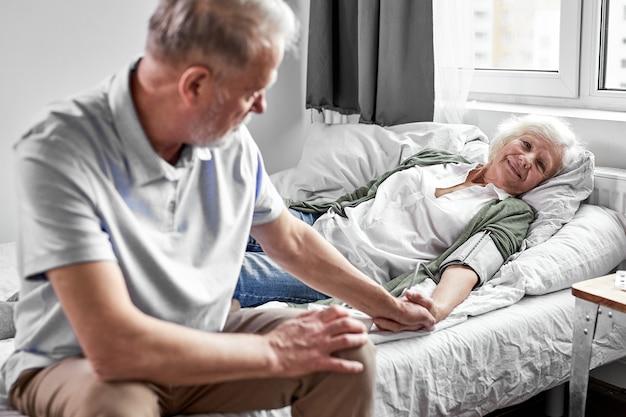 Zieke senior vrouw met haar zorgzame bejaarde man dicht bij haar, steun en hulp. geneeskunde concept