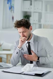Zieke slecht uitziende zakenman met baard zit aan bureau met documenten en houdt de hand op de borst terwijl hij hoest-, coronavirus- of longontstekingssymptomen heeft