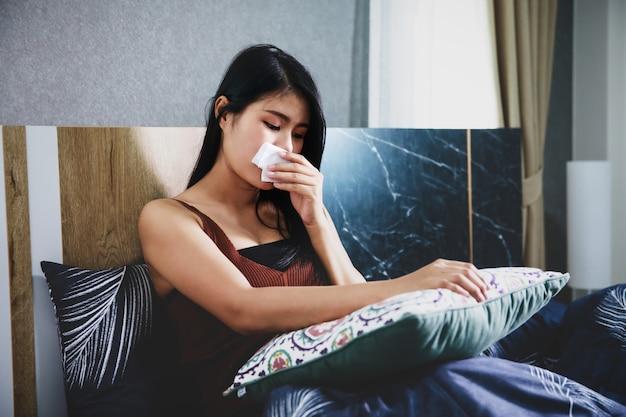 Zieke vrouw bedekt met een deken in bed liggen