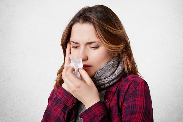 Zieke vrouw blaast haar neus in weefsel