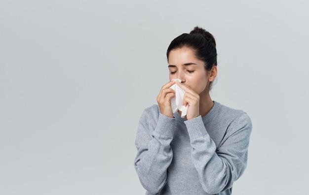 Zieke vrouw blaast haar neus met servet op grijze achtergrond en warme trui bijgesneden weergave. hoge kwaliteit foto