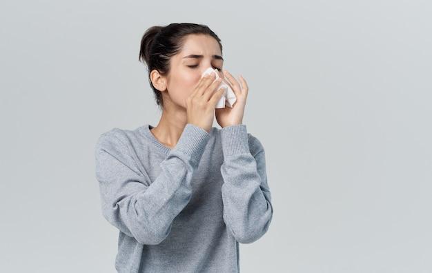 Zieke vrouw blaast haar neus met servet op grijze achtergrond en warme trui