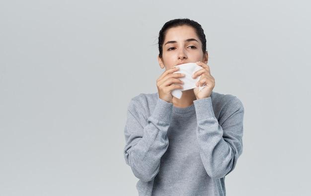 Zieke vrouw blaast haar neus met servet op grijze achtergrond
