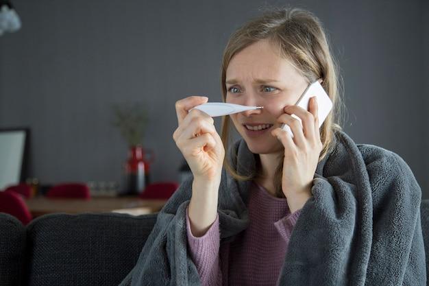 Zieke vrouw die echtgenoot na het meten van temperatuur roept