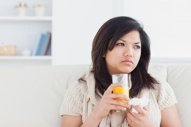 Zieke vrouw die een glas jus d'orange houdt