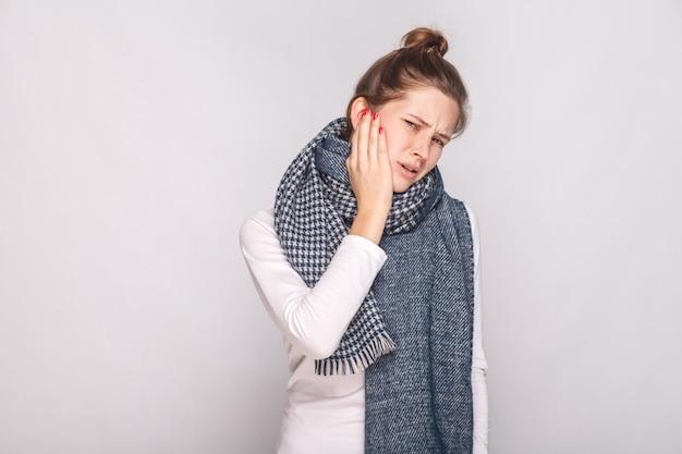 Zieke vrouw die haar cheeh hand vasthoudt, kiespijn heeft. studio opname, grijze muur