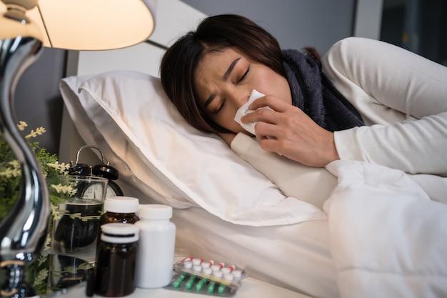 Zieke vrouw die koud voelt en in bed niest