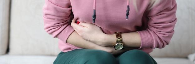 Zieke vrouw die op de bank zit en haar buik vasthoudt met haar handen close-up behandeling van