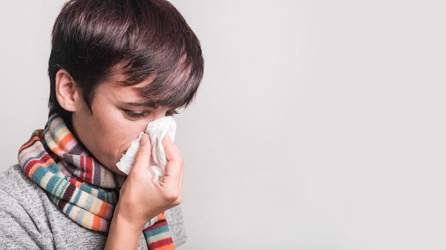 Zieke vrouw die sjaal draagt rond haar hals blazende neus in papieren zakdoekje tegen grijze achtergrond