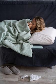 Zieke vrouw die thuis in bed ligt en lijdt aan allergie, griepsymptoom, koorts, niezen in papieren zakdoekje