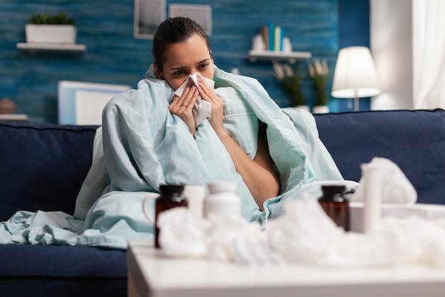 Zieke vrouw die thuis last heeft van symptomen van het coronavirus