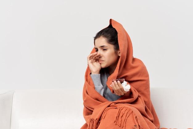 Zieke vrouw die thuis op de bank zit koude behandeling ontevredenheid