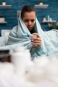 Zieke vrouw die thuis temperatuur meet met thermometer voelt zich ziek volwassene die koorts en virus controleert...