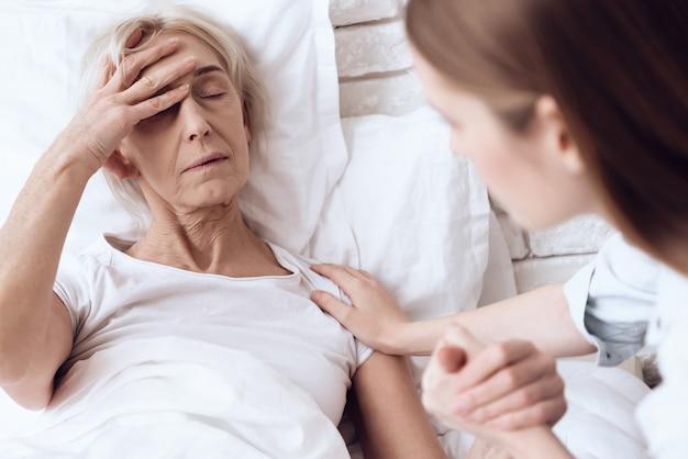Zieke vrouw heeft hoofdpijn in de kliniek