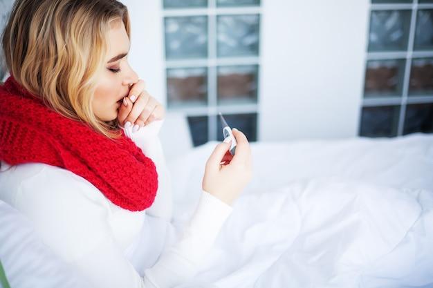 Zieke vrouw in bed met thermometer heeft koorts op hoge temperatuur