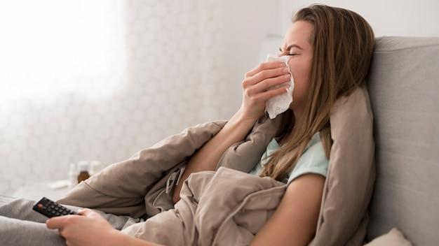 Zieke vrouw in bed zitten en haar neus snuiten