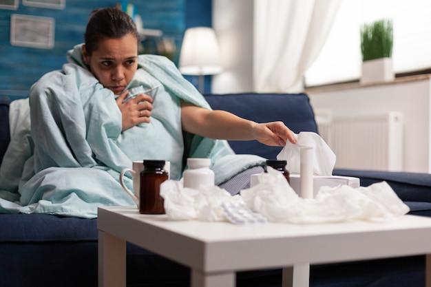 Zieke vrouw in deken die thuis zit met coronavirus