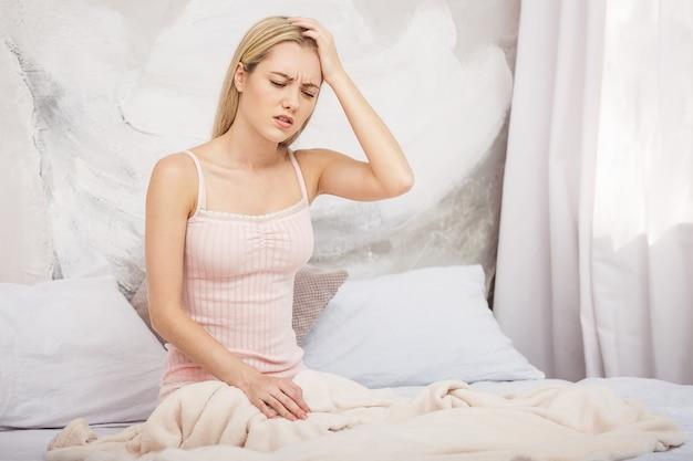 Zieke vrouw liggend in bed met hoge koorts