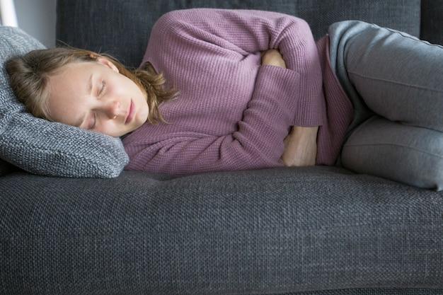 Zieke vrouw liggend op grijze bank thuis, met benen gebogen
