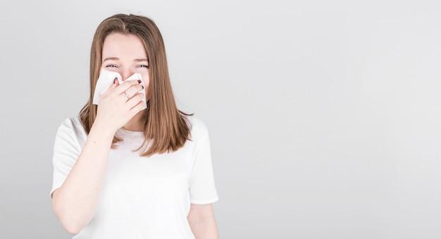 Zieke vrouw lijdt aan verkoudheid en snuit haar neus in een servet. het concept van geneeskunde en seizoensgebonden verkoudheid met copyspace.