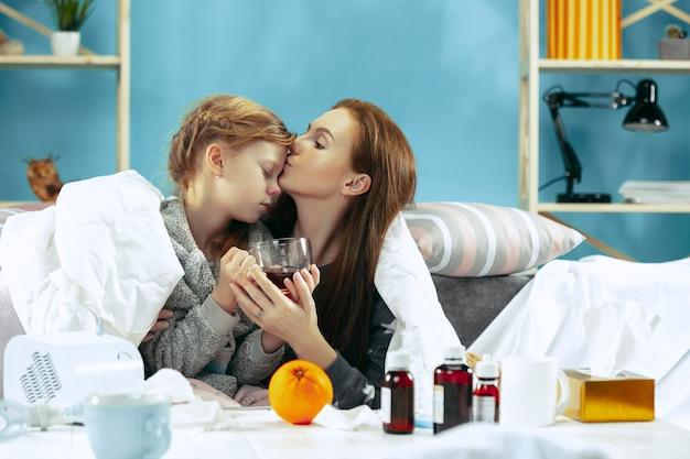 Zieke vrouw met dochter thuis. thuisbehandeling. vechten met een ziekte. medische gezondheidszorg. familieleden. de winter, griep, gezondheid, pijn, ouderschap, relatieconcept. ontspanning thuis
