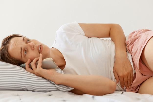 Zieke vrouw met donker haar met een wit casual t-shirt dat in bed ligt en via een smartphone met haar arts praat, maagproblemen heeft, buikpijn heeft.