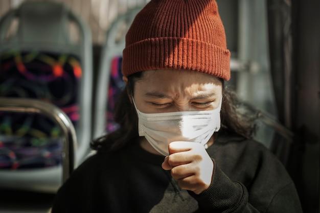 Zieke vrouw met een masker hoest in het openbaar tijdens een pandemie van het coronavirus